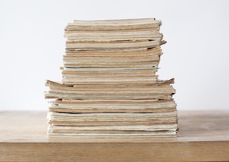 magazine stack: Stack of the old color paper documents on the wooden table