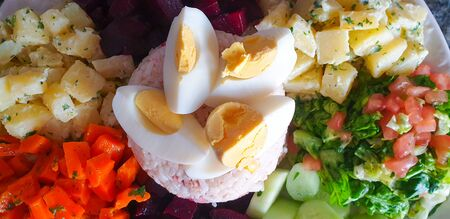 Salad of potatoes, eggs, carrot,  tomato, and mayonnaise on a plate closeup.