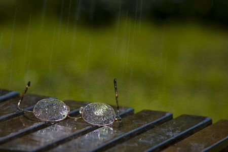 opthalmology: Pair of Glasses Sitting in the Rain Stock Photo