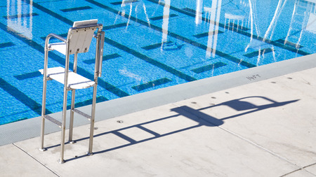 Empty lifeguard chair next to a bright blue pool