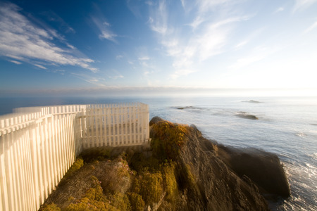 iceplant: White picket fence overlook on cliff above ocean at sunset with dreamy zoom effect (3167) Stock Photo