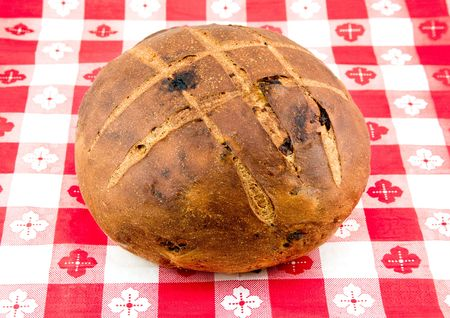 scored: Round loaf of rustic cinnamon raisin bread isolated on white