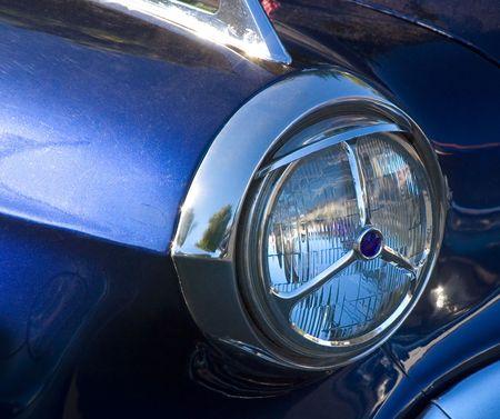 Closeup of a Vintage Car Headlight with Blue Dot  photo