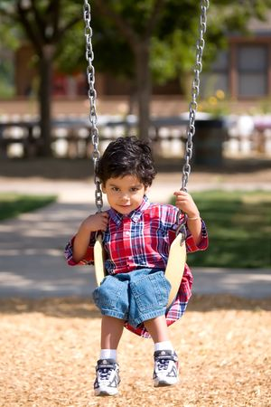 Young Boy on swing stares intently into the camera