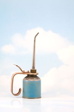 oilcan: Rusty old oil can against a sky background with clouds
