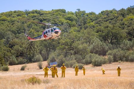 A wildland fire crew works with a helicopter