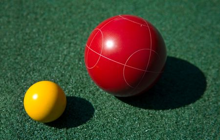 Closeup of a red bocce ball and a yellow palino Stock Photo
