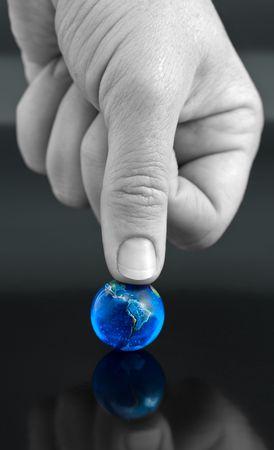 Thumb Pressing Down on Bright Blue Marble Globe