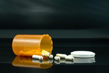 knocked over: Spilt Bottle of White Pills on a Black Background