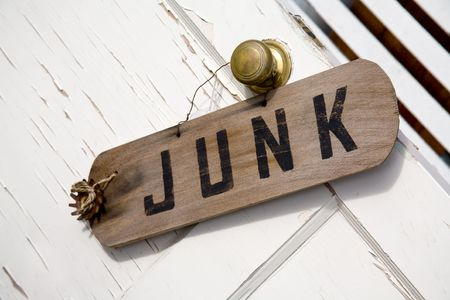 Sign with the Word Junk on an Peeling Door