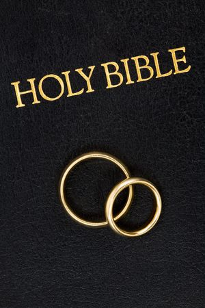christian marriage: Gold Wedding Rings on the Worn Cover of a Bible