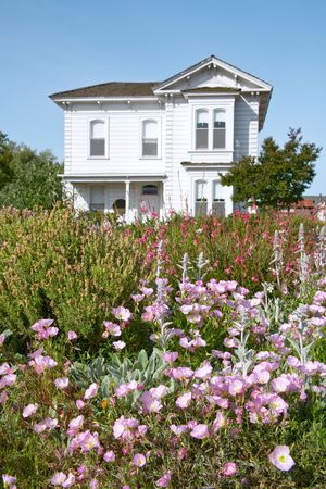 Flowers in Front of Old Victorian Farmhouse (in Public Park) Stock Photo