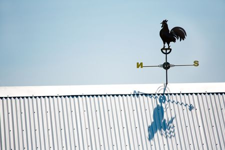 Rooser Weather Vane Atop Tin Roof in Clear Blue Sky