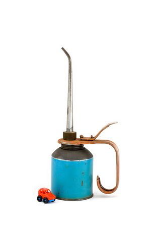Old Oil Can with Toy Car Isolated on White