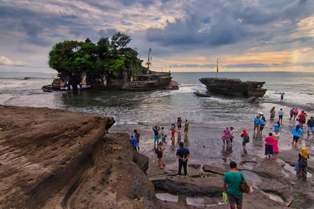 Tanah Lot, Bali - November 25th, 2017: Tourist assemble together at the beach waiting for low tide for them to reach Tanah Lot main temple. Tanah Lot is one of the famous tourism spot in Bali.