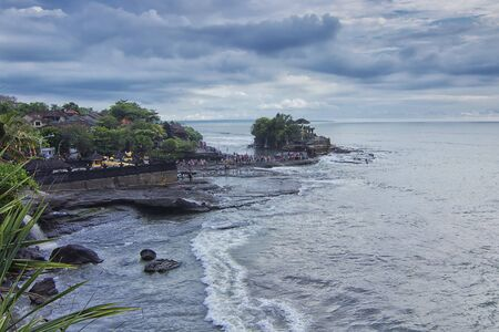 Great landscape view of the wave from the sea hitting hard the beach with Tanah Lot main Temple as the background