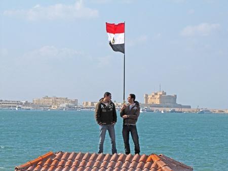 demonstrators: Alexandria, Egypt - February 11, 2011 - Egyptians demonstrators waving flag with Qaitbay Citadel in the background