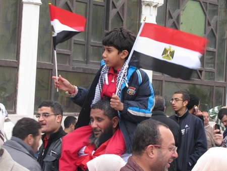 alexandria: Alexandria, Egypt - February 04, 2011 - Boy carrying flags among demonstrators calling for the resignation of President Mubarak