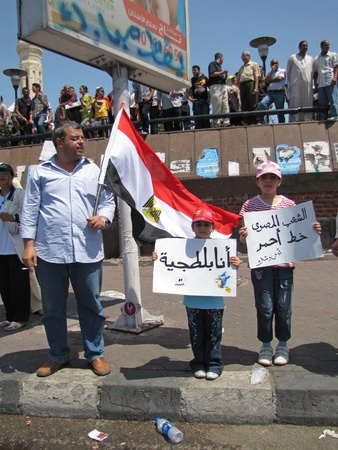prosecution: Alexandria, Egypt - July 8, 2011 - Egyptian demonstrators  calling for the prosecution of members of the former regime. Youg girl carrying Im a thug sign.