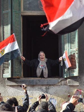 demonstrators: Alexandria, Egypt - Nov 25, 2011 - Egyptian old woman encouraging and supporting demonstrators passing by her window Editorial