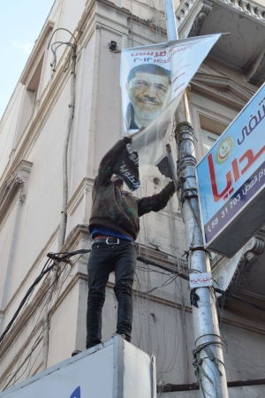 Alexandria, Egypt - December 7, 2012 -Egyptian demonstrator tearing down a poster of President Morsi