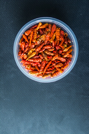 Red dried chili in a clear round plastic box on a gray background