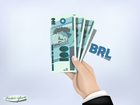 rea: brasilian reals money paper on hand,cash on hand