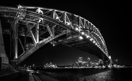 East side of Sydney harbour bridge at nihgt with bright reflecting in the blurred waters of harbour Foto de archivo