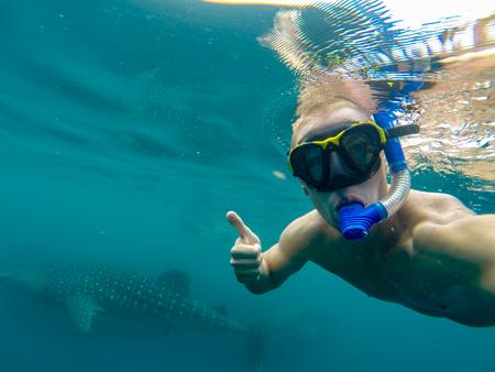Giovane uomo snorkeling sott'acqua con un grande squalo balena. Australia Ningaloo Reef