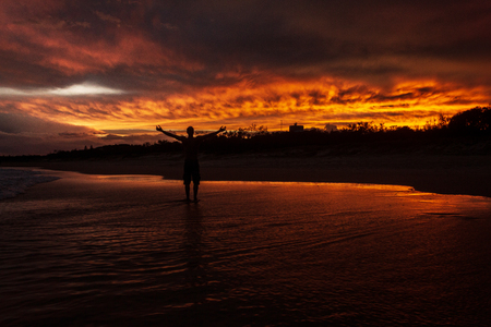 young man rising hands in the air because he is happy, with a colorfull sunset in the background at Noosaville beach, Sunshine Coast, Australia.
