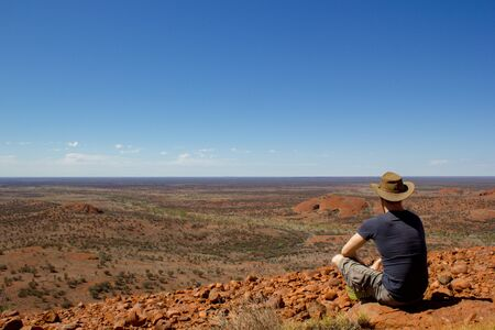 tourist enyoing view over the outback from a hill, after hiking up the olgas, the ,Red Center of Australia Archivio Fotografico