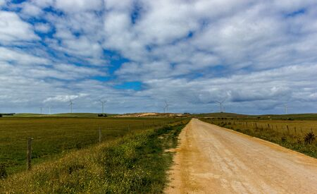 straight gravel road through to the Grampians Natioanl Park with a wind farm in the distance, New South Wales, Australia. Stok Fotoğraf - 132615032