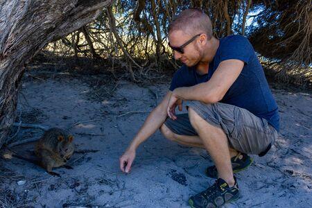young caucasian man with a Quokka in rottnest island, Perth, Australia Stok Fotoğraf