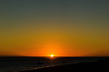 Natural Sunset over a beach with boats in the ocean, Western australia Stok Fotoğraf