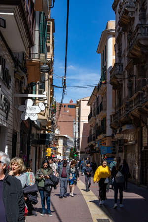 Palma, Mallorca - April 10, 2019: many tourists walking in a old thin street in town of Palma de Malorca