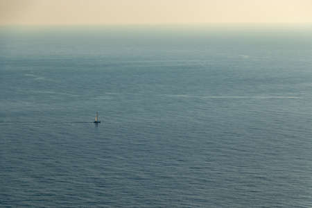 aerial view of a single Sailing boat in open blue sea from the viewpoint cap andritxol, mallorca, Spain