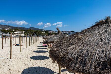 row of beach umbrellas on Palmanova beach in Calvia Bol ses Taules Mallorca, spain