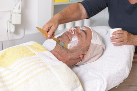 regeneration: Senior man lying on bed at beauty center while receiving facial treatment through the application of hydrating or regeneration cream Stock Photo