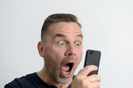 Surprised funny middle-aged man with blue eyes and a shocked facial expression looking at the screen of his mobile phone
