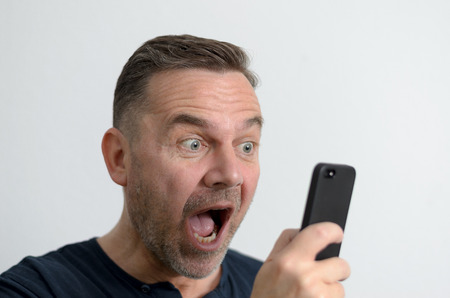explicit: Surprised funny middle-aged man with blue eyes and a shocked facial expression looking at the screen of his mobile phone, portrait with copy space on gray