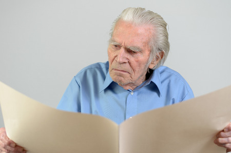 vision loss: Elderly man holding a blank paper sheet big holes and looking at it as at an empty newspaper portrait