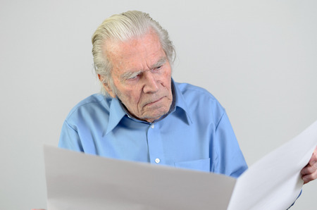 ageing: Elderly man holding a blank big white paper sheet and looking at it as at an empty newspaper portrait