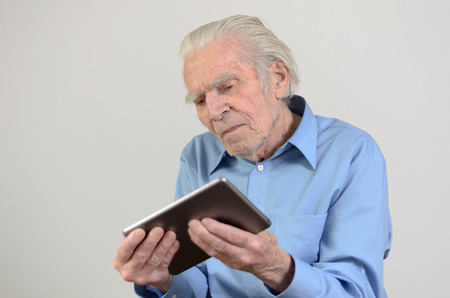 skeptical: Elderly man with blue shirt holding a modern tablet PC while looking at it with a nostalgic facial expression in front of the New Technologies portrait with copyspace on gray