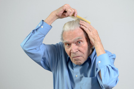 daily routine: Active Healthy elderly man wearing a clean blue shirt while combing his hair with a plastic comb part of daily routine portrait with copyspace on gray Stock Photo