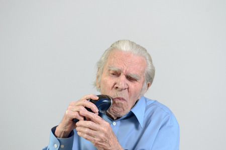 senescence: Elderly groomed man wearing a tidy blue shirt while shaving himself with a cordless battery powered electric razor or shaver portrait with copyspace on gray