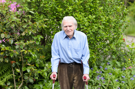 forearm: Elderly man with casual clothes using forearm crutches as a mobility aid to walk on the cobblestones of a footpath in a green park or yard full length
