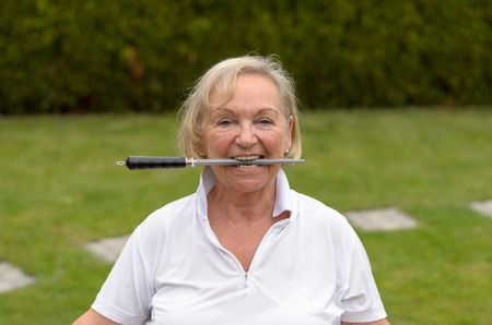 clenching teeth: Head and Shoulders Portrait of Mature Woman Acting Playful Grasping Knife Sharpener Between Teeth