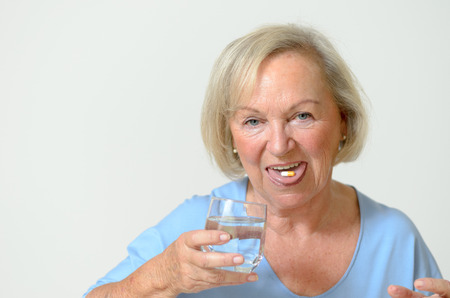 prescribed: Elderly lady taking the prescribed dose of medicine with a glass of water to treat a chronic disease Caused by aging portrait with copyspace on gray