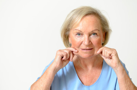 Senior woman wearing blue shirt while showing her face Effect of Aging Caused by loss of elasticity closeup Фото со стока