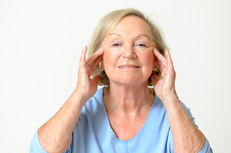 aging face: Senior woman wearing blue shirt while showing her face Effect of Aging Caused by loss of elasticity closeup Stock Photo